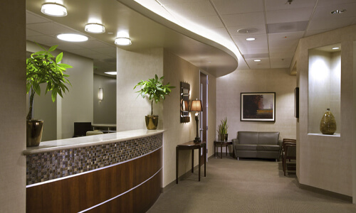 Picture of a dental center reception area in San Jose, Costa Rica.  The interior of the reception area is well lighted with light brown and cream colors.