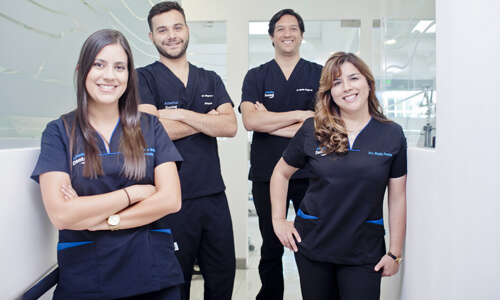 Picture of a dental team representing the dental services of the Costa Rica Dental Center in San Jose, Costa Rica.  The team consists of 2 male dentists and 2 female dentists, who are wearing dark blue work uniforms.