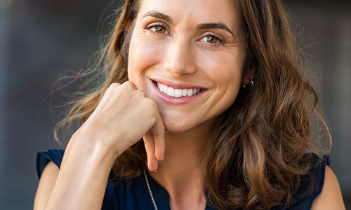 Picture of a smiling woman, happy with the cosmetic dental treatments she had at the Costa Rica Dental Center in San Jose, Costa Rica.  The woman has long brown hair and is wearing a black blouse.  She has perfect teeth and is smiling directly at the camera.